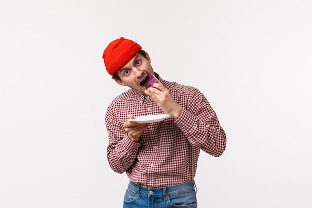 Celebração, feriados e conceito de estilo de vida cara engraçada jovem hippie no gorro vermelho e camisa xadrez, segurando a placa, comendo bolo delicioso olhar câmera com desejo, em pé