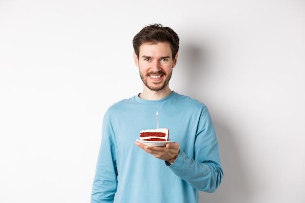 Celebração. jovem bonito, comemorando o aniversário, segurando um bolo de aniversário com uma vela acesa e sorrindo, fazendo desejo, em pé sobre um fundo branco.