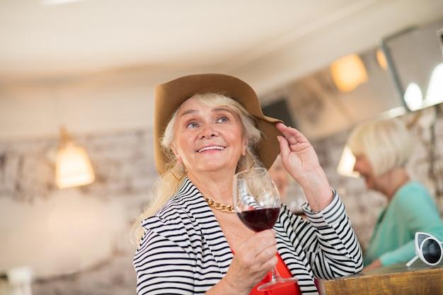 Celebração. mulher alegre com um chapéu marrom segurando uma taça de vinho