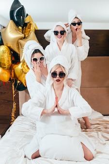 Celebração no spa. diversão de festa e relaxamento. mulheres sorridentes, posando na cama. vestidos com óculos de sol, roupões de banho e toalha turbante.