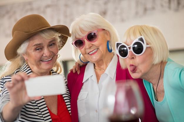 Celebração. três senhoras idosas felizes se divertindo e bebendo vinho
