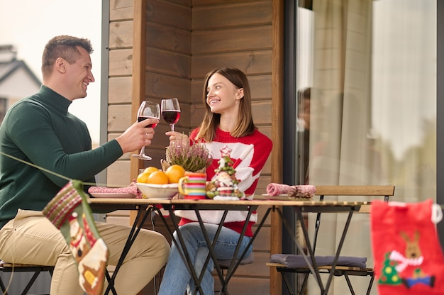 Celebração. um casal sentado à mesa com taças de vinho nas mãos