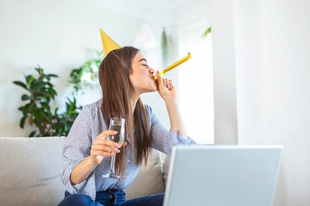 Celebração virtual. mulher feliz com chapéu de festa comemorando aniversário online em quarentena ou auto-isolamento, usando laptop para videochamada com amigos e familiares, segurando champanhe