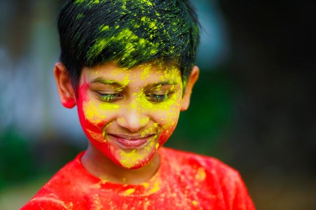 Celebrações de holi - menino índio brincando de holi e mostrando a expressão facial.