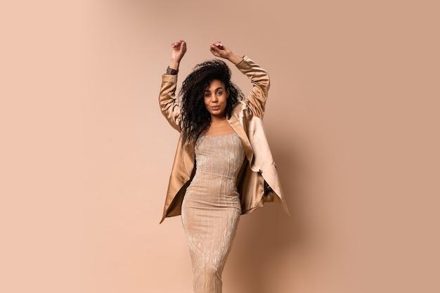Celebrando mulher com incríveis cabelos ondulados volumosos dançando e se divertindo.