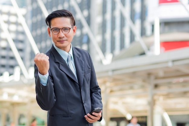 Celebrando o sucesso. empresário feliz em pé ao ar livre com edifício de escritórios em segundo plano