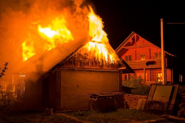 Celeiro de madeira queimando à noite. chamas de fogo laranja alta, fumaça densa debaixo do telhado de azulejos no céu escuro, silhuetas de árvores e fundo residencial casa de madeira vizinho. conceito de desastre e perigo.