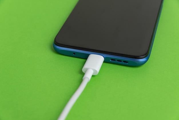 Celular azul conectado ao tipo de cabo usb - carregando