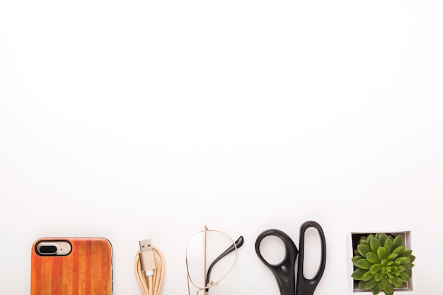 Celular; cabo usb; óculos; tesoura e vaso de plantas no fundo do fundo branco