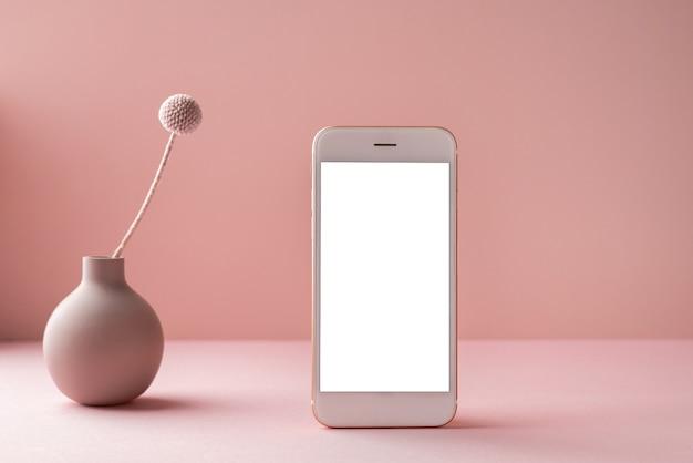 Celular com tela branca e flor seca em um vaso em fundo rosa