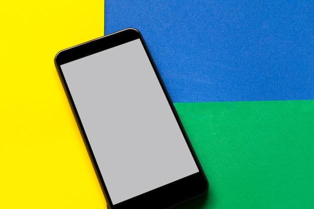 Celular com tela branca sobre fundo verde, amarelo e azul.