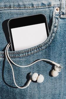 Celular com tela de maquete em branco no bolso da calça jeans com fones de ouvido