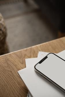 Celular com tela em branco na mesa de madeira