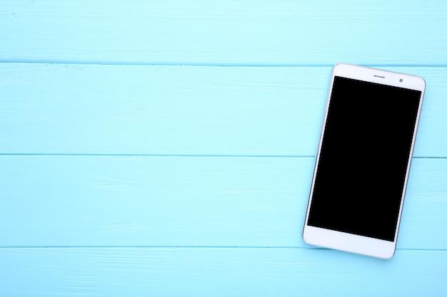 Celular com tela em branco sobre fundo azul de madeira. smartphone na mesa de madeira.