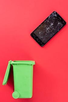 Celular com tela quebrada e lixeira verde. reciclando.