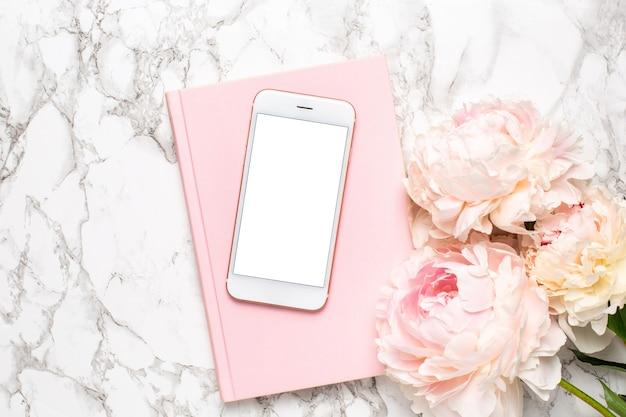 Celular com um caderno branco e rosa e flores piony em uma vista superior do fundo de mármore