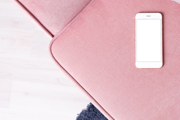 Celular de tela em branco branco sobre fundo poltrona rosa pastel. estilo mínimo, vista superior plana