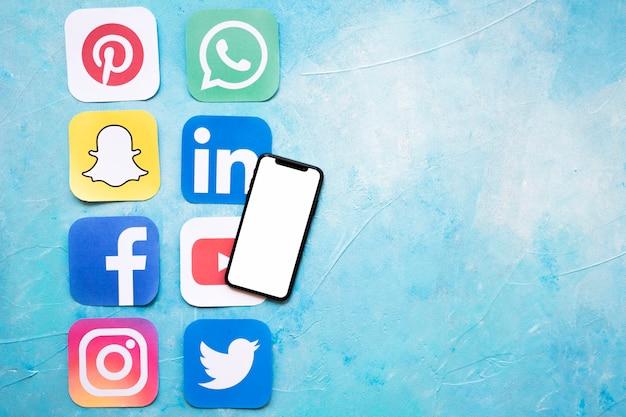 Celular de tela em branco com ícones de aplicativo de mídia sobre tinta texturizada azul