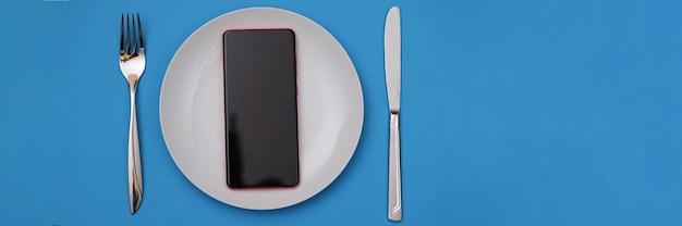 Celular deitado em uma placa branca perto de garfo e faca