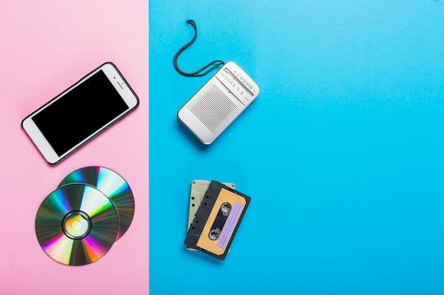 Celular e cd substituídos por gravador e cassete em duplo pano de fundo rosa e azul