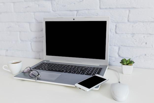 Celular e óculos no laptop aberto com xícara de café sobre a mesa branca