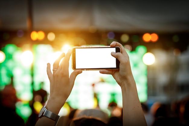 Celular na mão durante as filmagens de um show