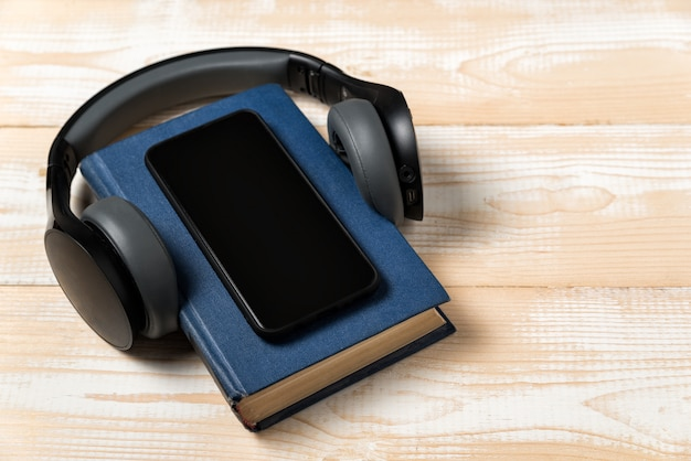 Celular no livro com fones de ouvido. conceito de audiobook. luz de fundo de madeira.