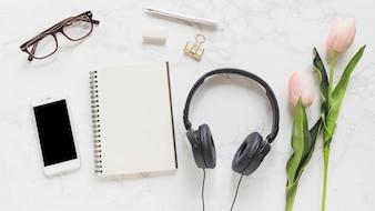 Celular; Óculos; caderno; papelaria; fone de ouvido e tulipas cor de rosa no pano de fundo de mármore