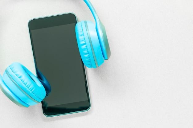 Celular ou smartphone com fone de ouvido na mesa branca com espaço livre