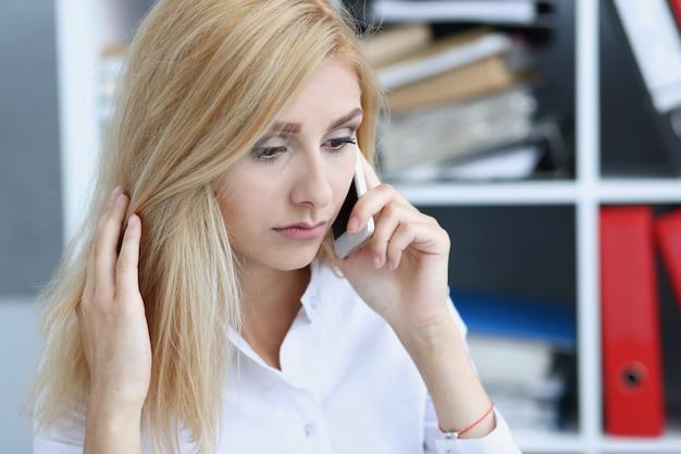 Celular pensativo loiro bonito da conversa da mulher de negócios