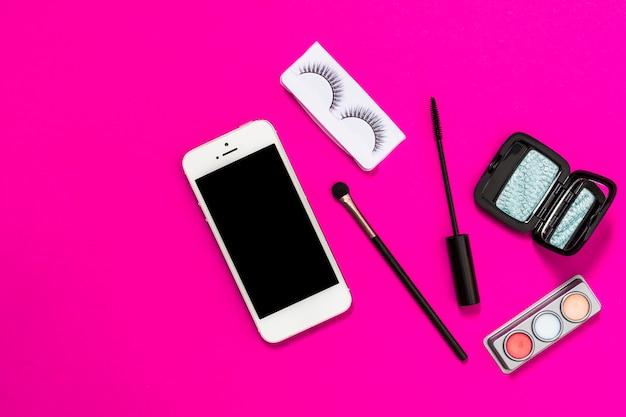 Celular; pincel de maquiagem; cílios; escova de rímel e paleta da sombra no pano de fundo rosa