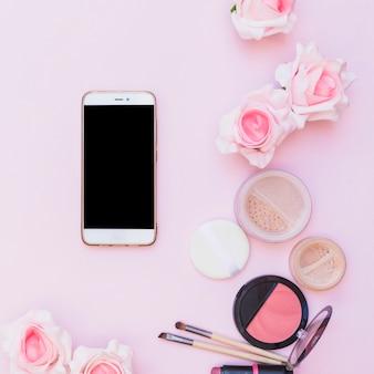 Celular; produtos cosméticos e flores sobre fundo rosa em fundo rosa