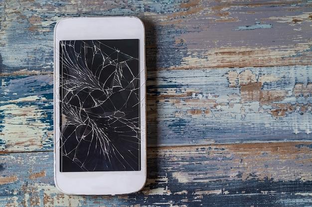 Celular quebrado com display rachado no fundo azul de madeira, plano leigo.