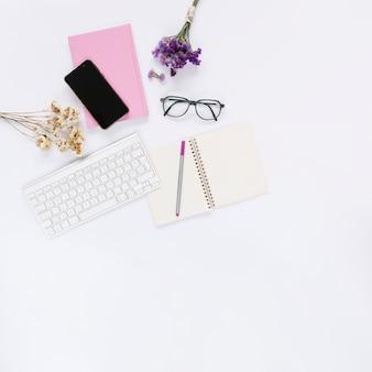 Celular; teclado com artigos de papelaria e flores sobre fundo branco