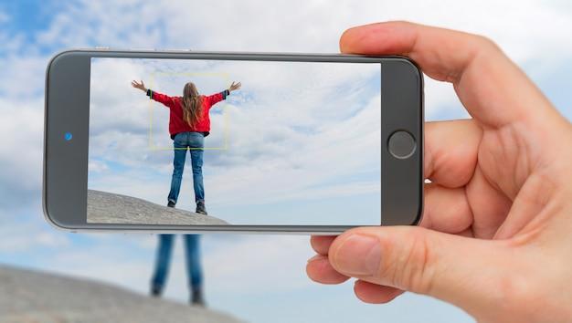 Celular tirando foto de garota de casaco vermelho com os braços erguidos