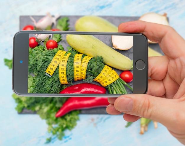 Celular tirando foto de legumes