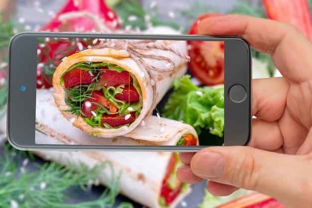 Celular tirando foto do rolo de legumes