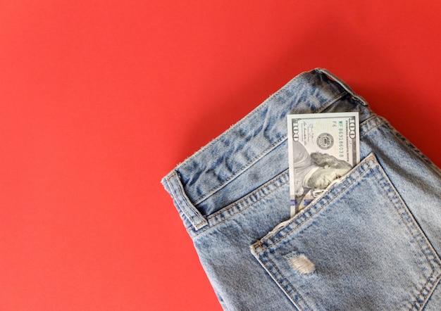 Cem dólares no bolso de calça jeans no vermelho