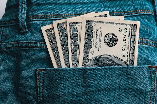 Cem notas americanas em dinheiro no bolso de trás da calça jeans.