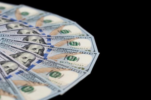 Cem notas de dólar são espalhadas em um fundo preto. vista lateral superior.