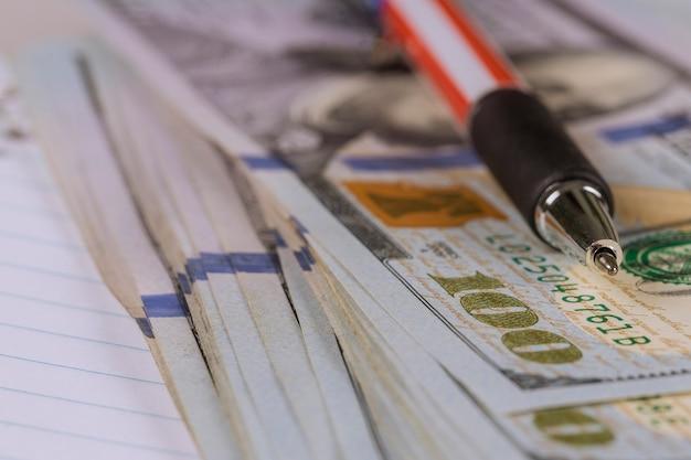 Cem notas de dólares americanos e caneta deitada