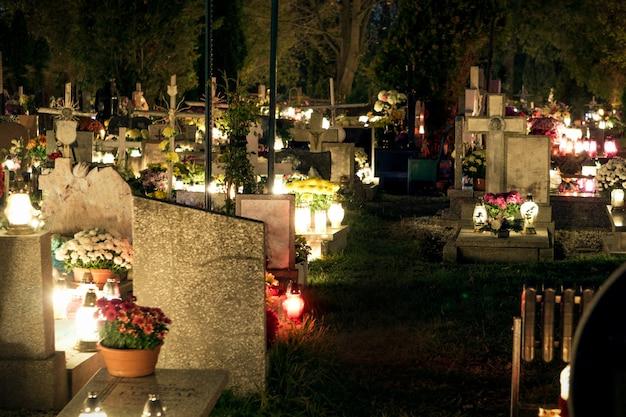 Cemitério à noite, queimando velas, lápides iluminadas à luz de velas