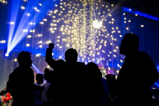 Cena borrada da noite do conceito na festa de concertos com audiência e iluminação conduzida colorida.
