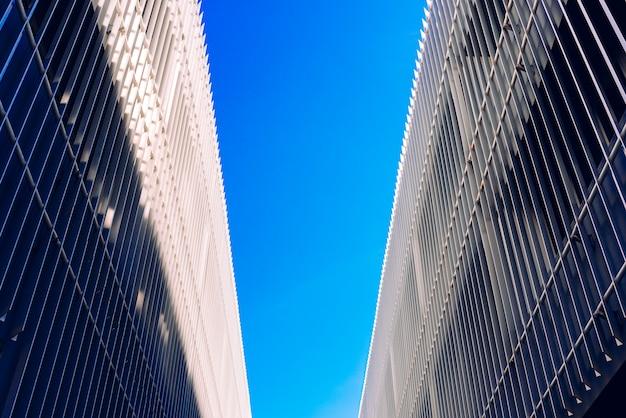 Cena com céu azul no centro e em cada lado edifícios simétricos