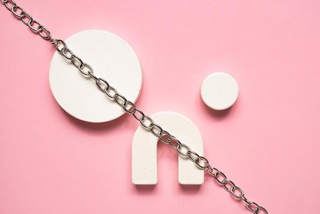 Cena com formas geométricas. fundo abstrato com figuras de beton brancas e corrente de metal em um fundo rosa. vista superior da composição geométrica