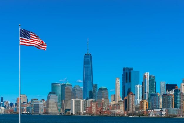 Cena da bandeira da américa sobre o lado do rio de paisagem urbana de nova york, que local é mais baixo manhattan, arquitetura e construção com turista e dia da independência