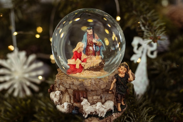 Cena da natividade de jesus cristo em uma bola de vidro em uma árvore de natal