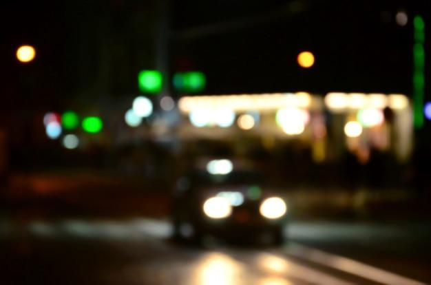 Cena da noite turva de tráfego na estrada. imagem desfocada de carros viajando com faróis luminosos. bokeh art
