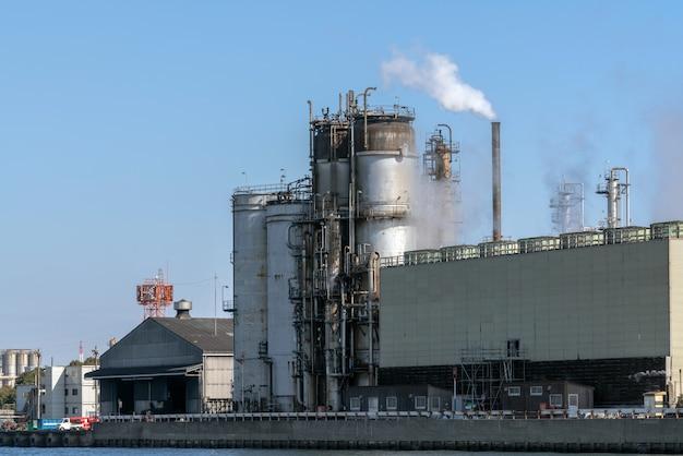 Cena da zona industial da refinaria de petróleo ao lado do rio na hora de funcionamento que têm o fumo de vapor