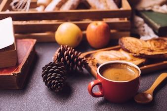 Cena de café da manhã com uma xícara de café, pão e frutas na mesa